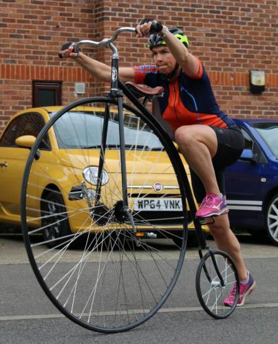 woman mounting penny farthing